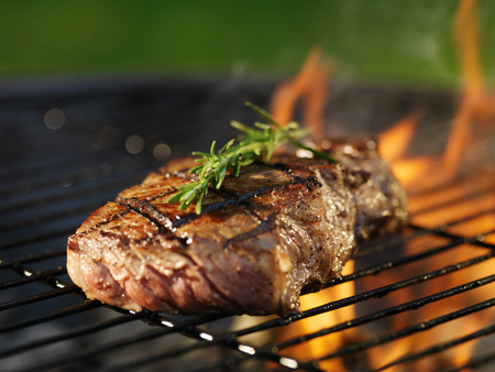 steak with flames on grill with rosemary photo