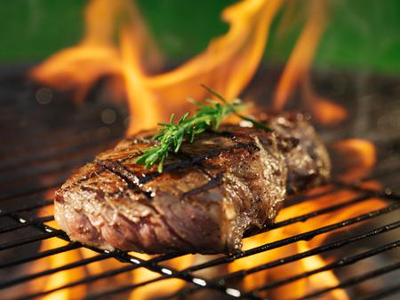 barbecue: Filete con las llamas en la parrilla con romero
