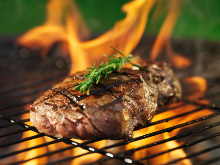barbecue fire: steak with flames on grill with rosemary