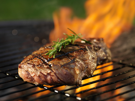 steaks: steak with flames on grill with rosemary