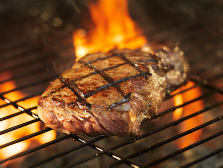 grill: beef steak cooking over flaming grill