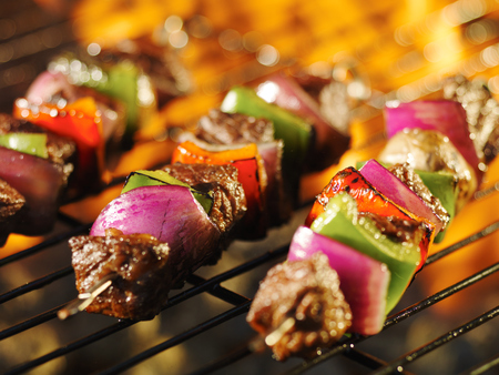 steak shishkabob skewers cooking on flaming grill
