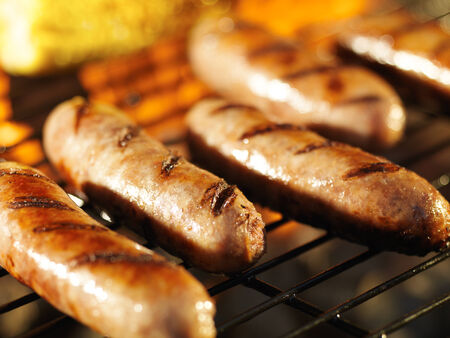 bratwursts on grill with corn close up photo