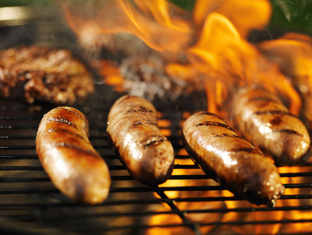 bratwursts cooking on flaming grill Imagens