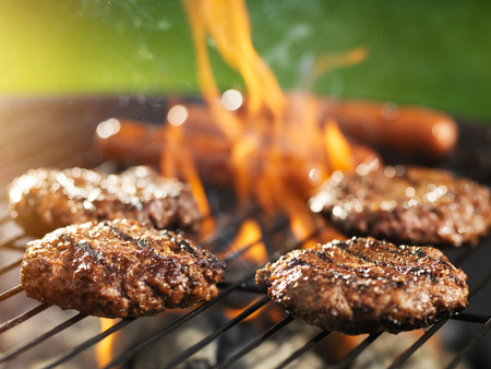 hamburgers and hotdogs cooking on flaming grill photo