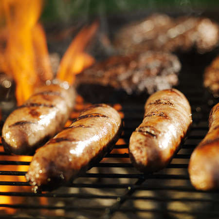 cooking bratwursts over flaming grill photo