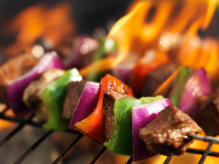 steak shish kabobs on grill with flames photo