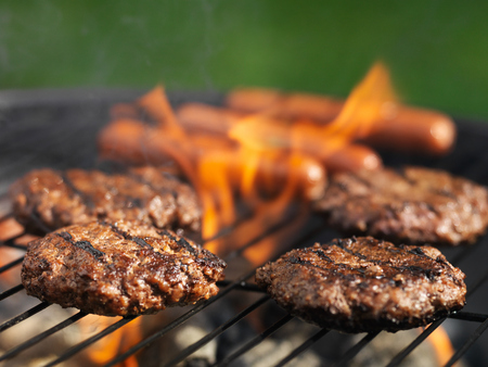 hamburgers and hotdogs cooking on grill outdoors Stock Photo