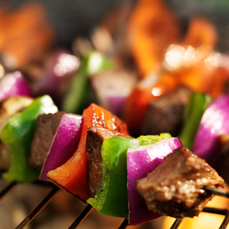 beef shish kebabs skewers cooking on grill with flames
