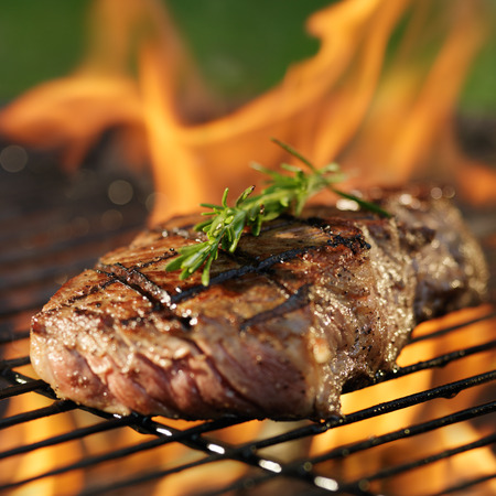 steak cooking over flaming grill photo