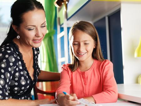 tutor: madre ayudando a su hija feliz con la tarea