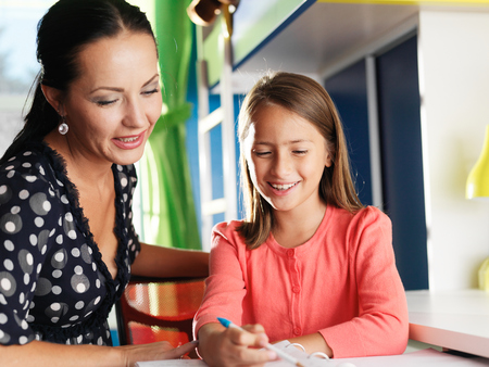 mother helping happy daughter with homework