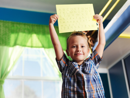 proud little boy showing his completed alphabet worksheet Stock Photo
