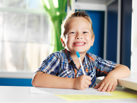 person writing: little boy doing homework in room with happy face