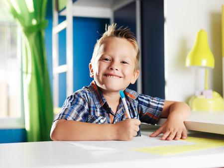 kindergartener: little boy doing homework in room with happy face