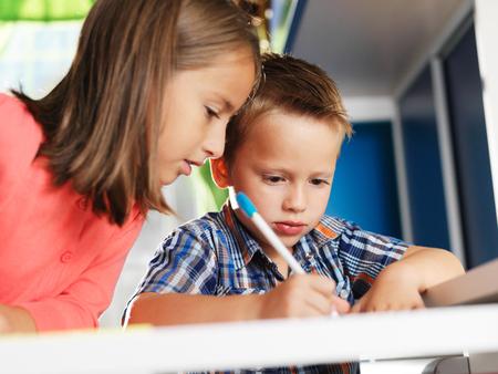 niños escribiendo: hermana mayor ayudando hermano pequeño con la tarea Foto de archivo