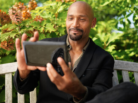mature african taking selfie with smartphone photo