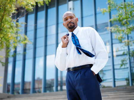 confident african businessman with tie blowing in the wind photo