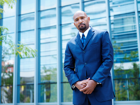african businessman: african american businessman in front of glass office building