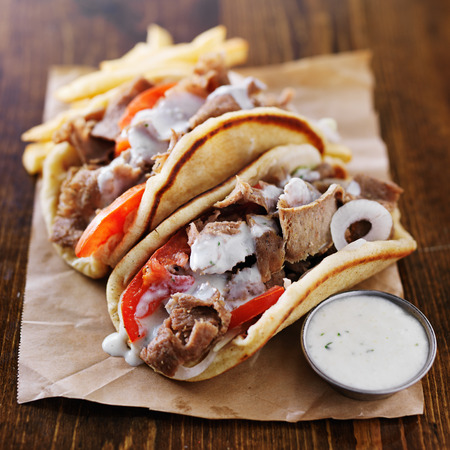 pita bread: greek gyros with tzatziki sauce and fries on parchment
