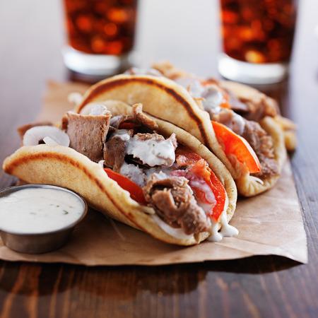 alimentos y bebidas: gyros griegos con salsa tzatziki y patatas