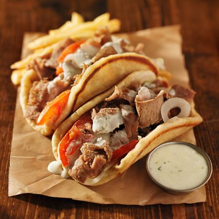 Griekse gyros met tzatziki saus en frietjes op perkament Stockfoto