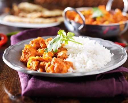 curry chicken: indian chicken vindaloo curry with basmati rice on plate