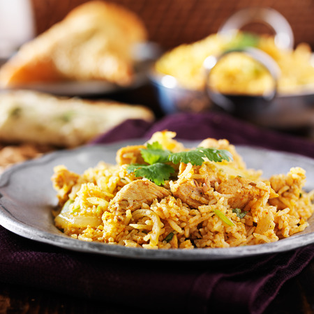 india food: indian chicken biryani with naan and samosa in background