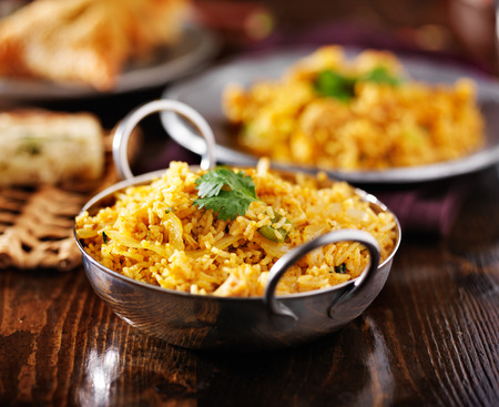 indian chicken biryana in balti dish with naan and samosa in background Stockfoto