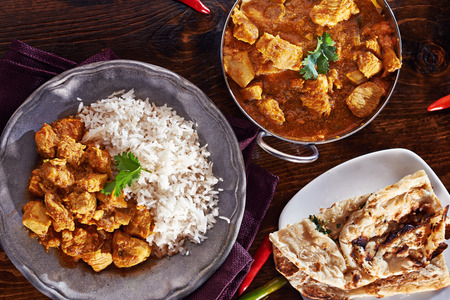 food on table: Pasto indiano del curry con piatto balti, naan e riso basmati