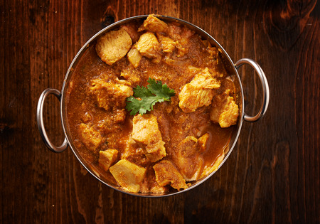 overhead photo of a batli dish with indian butter chicken curry
