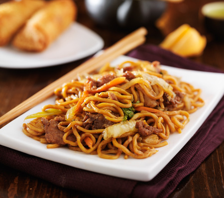 close up food: stirfried chinese beef lo mein with chopsticks