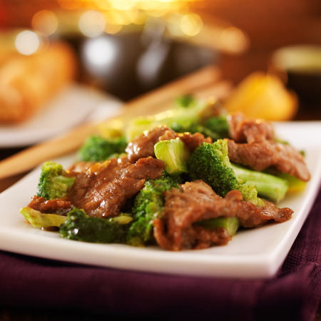 take out food: chinese beef and broccoli  stir fry in warm light Stock Photo