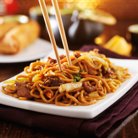 eating chinese beef lo mein with chopsticks