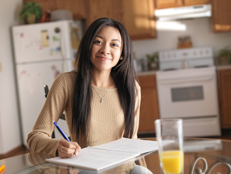 african american teen in kitchen studying and smiling at camera photo
