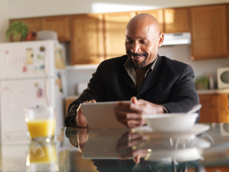 happy african guy with tablet in kitchen with breakfast photo