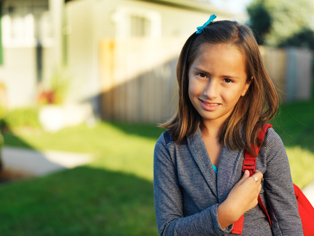 back posing: little schoolgril with backpack outside ready to go to school Stock Photo