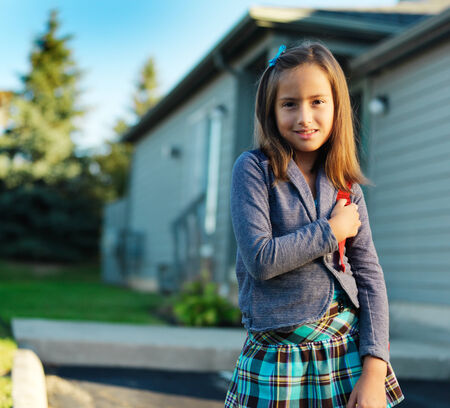 school girl with backpack standing infront of house photo