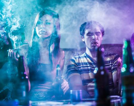 personas festejando: adolescentes que fuman marihuana en el humo llenó la habitación