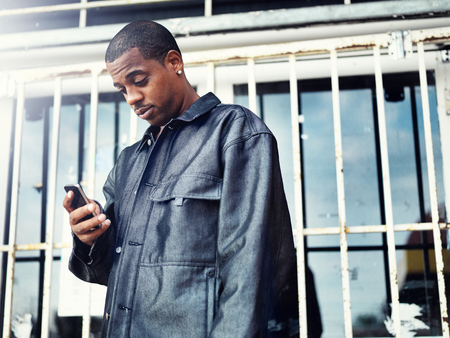 rough african american man with smartphone in front of abandoned store photo