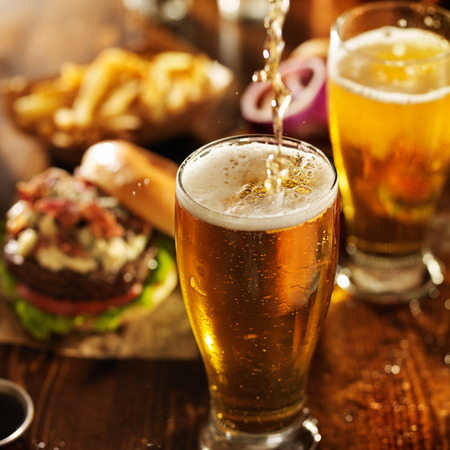 pouting beer into glass with burgers on wooden table top 스톡 콘텐츠