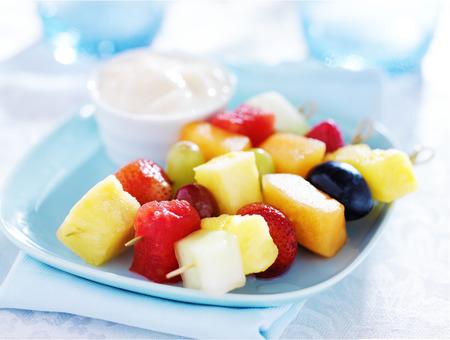 fruits de la brochette des enfants à la vanille trempette au yogourt sur la plaque bleue
