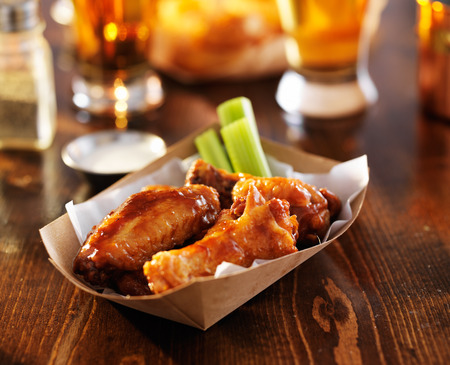 fried chicken wings: buffalo chicken wings in disposable tray with celery and ranch