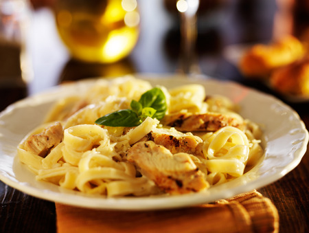 fettuccine alfredo pasta with grilled chicken at night time dinner