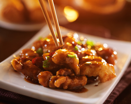 eating chinese food general tso's chicken with chopsticks