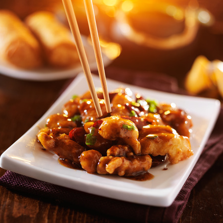 asian food: chinese take out food - eating general tsos chicken with chopsticks Stock Photo