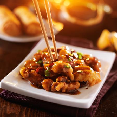 plato de comida: Los chinos sacan los alimentos - comer pollo del General Tso con palillos
