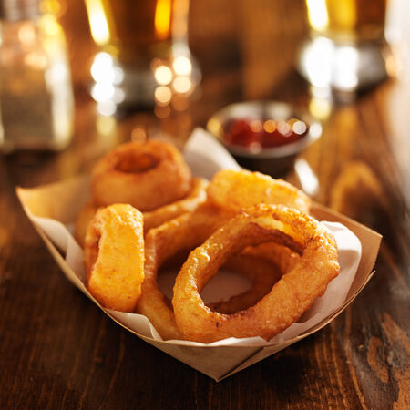 alcohol cardboard: basket of crispy onion rings with beer in the backgound