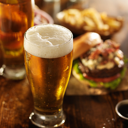 cold beer with foamy head and burgers photo