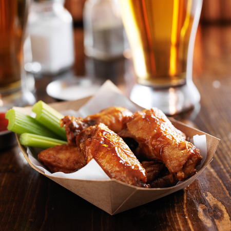 fried chicken wings: buffalo chicken wings in basket with celery and ranch